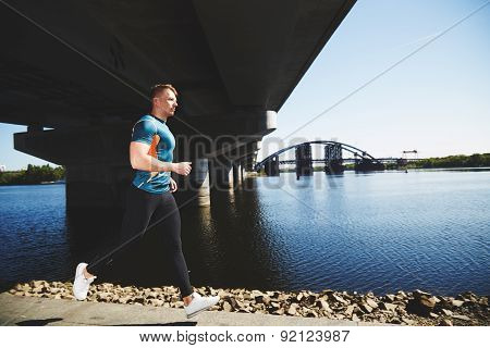 Young handsome man running along the embankment