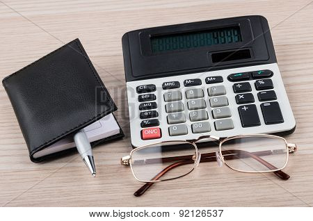 Calculator, Notepad, Pen And Glasses On Table
