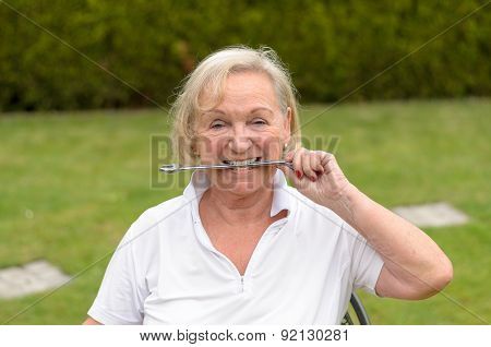Senior Serene Woman Biting On A Wrench