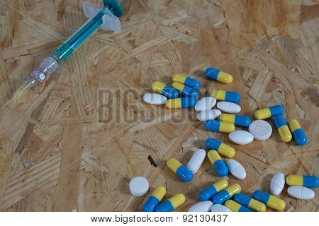 Pills, Syringe And Cooked Heroin On Wooden  Table