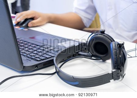 Man Hand Using Keyboard And Mouse To Control Laptop With Headphone Beside