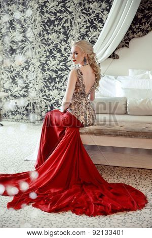 Elegant Blond Woman Model Wearing In Luxurious Red Gown With Long Train Of Dress Sitting At Modern I