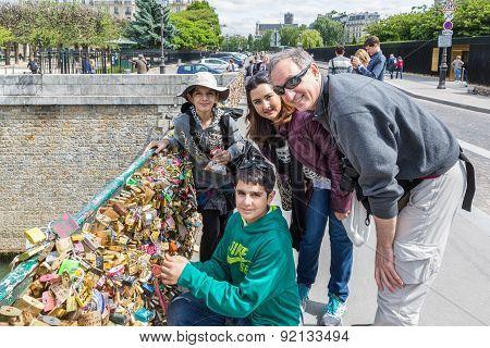 Family Locking Love Padlock At Seine Bridge In Paris, France