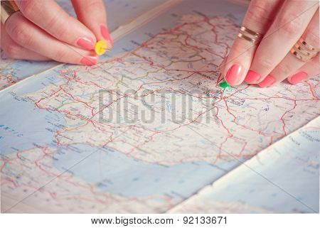 Hands pinning travel destination points on map, filtered, photo