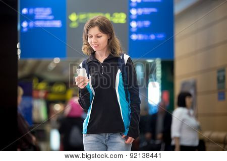 Girl Using Mobile Phone In Airport