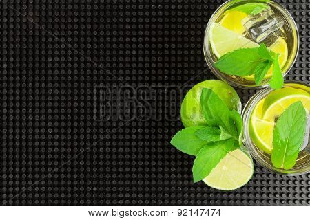 Mojito cocktail and ingredients over black rubber mat with copy space