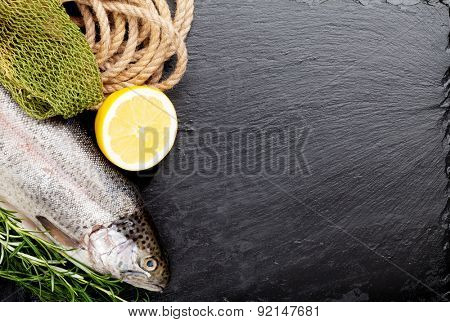 Fresh raw rainbow trout fish with spices on black stone with copy space. Toned