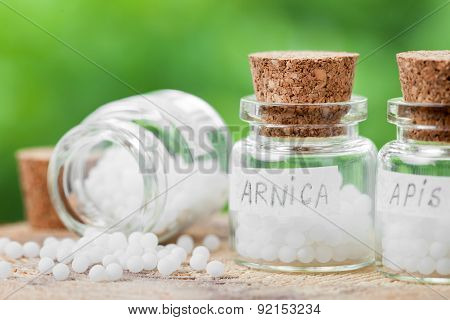 Three Bottles Of Homeopathy Globules On Green Background