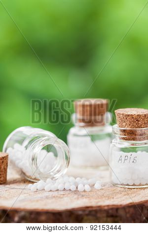 Bottles Of Homeopathy Globules On Green Background