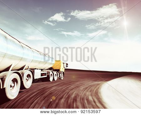Yellow Truck On Blurry Asphalt Road Over Cloudy Sky
