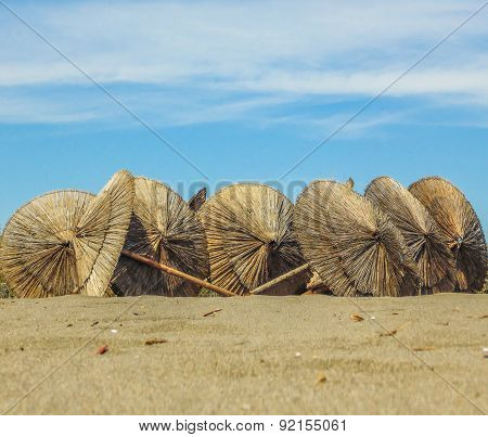 Wooden parasols on sandy seaside