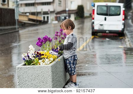 Cute little boy playing under the rain in a city