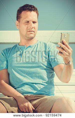 Man Tourist On Pier Using Smartphone. Technology.