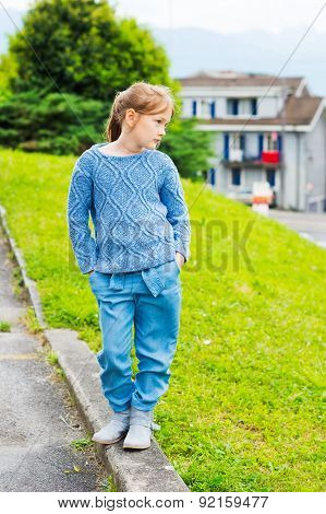 Fashion portrait of a pretty little girl of 7 years old, wearing blue knitted pullover