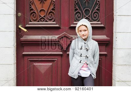 Outdoor portrait of a cute little girl in a city, wearing grey knitted jacket