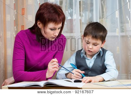 Mother helps pupils to do homework