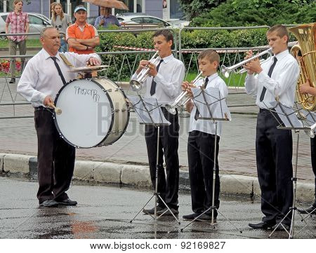 Performance Of Children's Brass Band Beating In The Rain