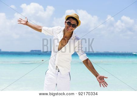 Young handsome man wearing white fresh clothes in a sunny day at the beach