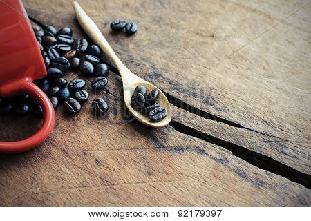 Red Cup Of Coffee With Wooden Spoon And Coffee Bean