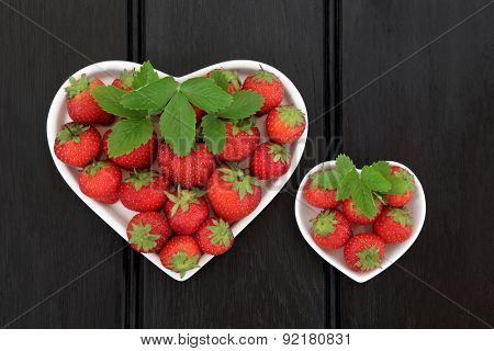 Strawberry fruit in heart shaped porcelain dishes over dark wood background,.