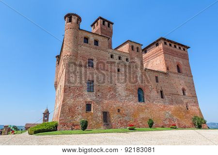Old medieval castle under blue sky in Piedmont, Northern Italy.