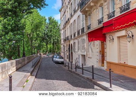 Narrow cobblestone street among green trees and parisian building in Paris, France.