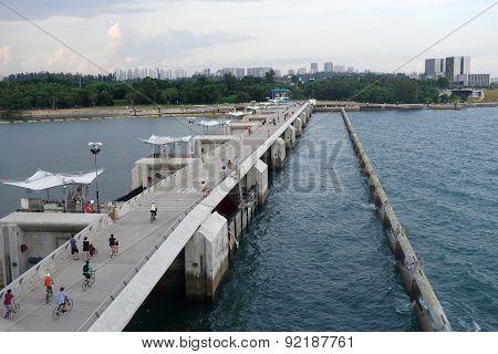 People Jog And Cycle On The Bridge Of Marina Barrage