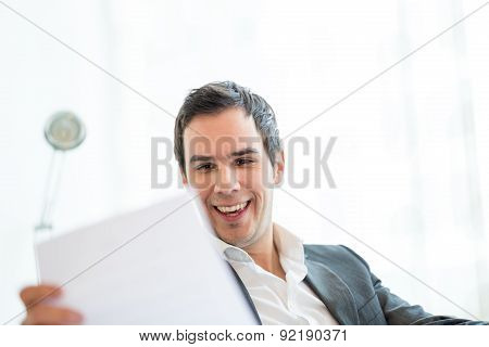 Happy Businessman Reading A Document At His Office