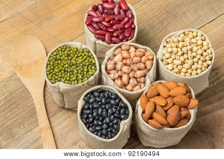 Different Kinds Of Beans In Sacks Bag On Wooden Background