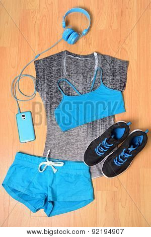 Gym outfit - workout clothing, running shoes, headphones and smartphone to listen to music while working out at the fitness center. Matching clothes, sports bra, shorts in blue and black.