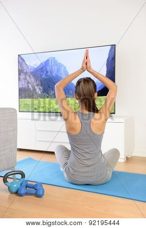 Woman doing home yoga meditation in front of TV. Fit girl doing easy pose relaxation exercises watching a TV show or training video with arms raised sitting on the floor of the living room.