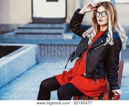 Girl Sitting on Bench. Street Fashion. Urban Lifestyle. Young Beautiful Woman Walking Outdoor.Image toned.