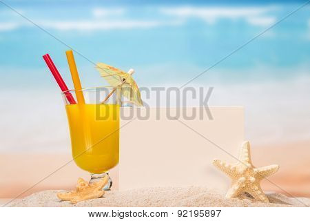 Juice and blank paper in the sand