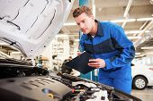 stock photo of concentration man  - Concentrated young man in uniform examining car and writing something in clipboard while standing in workshop  - JPG