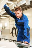 foto of concentration man  - Concentrated young man in uniform examining car while standing in workshop  - JPG