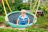 image of swing  - Funny happy kid boy having fun chain swing on outdoor playground - JPG