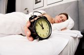 image of early 20s  - Man lying on the bed with alarm clock - JPG
