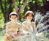 pic of fountain grass  - Happy kids playing and splashing with water sprinkler on summer grass yard - JPG