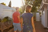 image of heterosexual couple  - Rear view of young couple walking towards their house - JPG