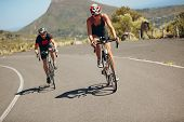 foto of triathlon  - Cyclist riding bikes on open road - JPG