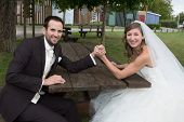 image of wrestling  - Young happy newly wed couple fighting in arm wrestling - JPG