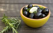 pic of kalamata olives  - A bowl of olive on a wooden board with rosemary