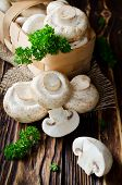 picture of champignons  - Champignons with parsley in a basket on a wooden table - JPG