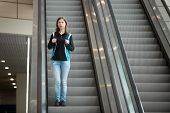 stock photo of escalator  - Young woman in 20s with backpack riding escalator in airport terminal travelling alone wearing casual style clothes