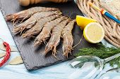 pic of tiger prawn  - Fresh raw tiger prawns and fishing equipment on wooden table - JPG