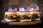 stock photo of beef-burger  - Mini beef burgers with American flag on wooden backgoundselective focus  - JPG