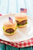 picture of beef-burger  - Mini beef burgers with American flag in white plateselective focus - JPG
