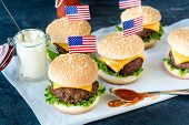 image of beef-burger  - American mini beef burgers with cheese and USA flagsselective focus - JPG