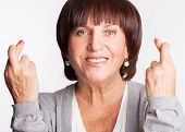 picture of fingers crossed  - Mature woman with crossed fingers - JPG