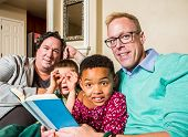 image of gay couple  - Attractive gay couple reads a book to their children - JPG